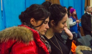 Two women pray at a Mission Ukraine outreach event in Kiev.